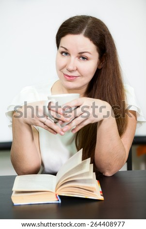 Young woman reading book while sitting at table with tea cup - stock photo