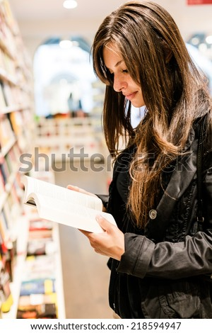 Young woman reading books in a bookstore - stock photo