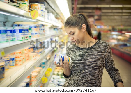 Young woman reading ingredients,declaration or expiration date on a dairy product before buying it.Curious woman reading nutritional values of the food.Shopping in the supermarket grocery store. - stock photo