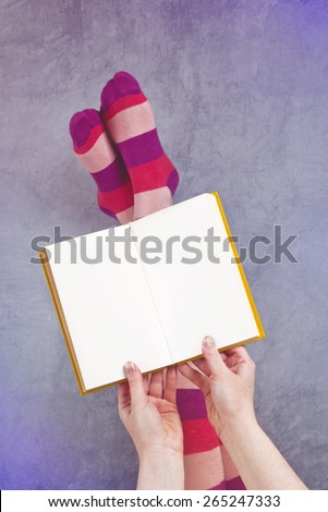 Young Woman Reading Pulp Fiction Book with Her Feet Raised in The Air, Blank Pages as Copy Space. - stock photo