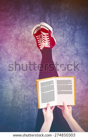 Young Woman Reading Pulp Fiction Book with Her Feet Raised in The Air, Generic Text on Pages - stock photo