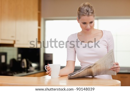 Young woman reading the news while having tea in her kitchen - stock photo