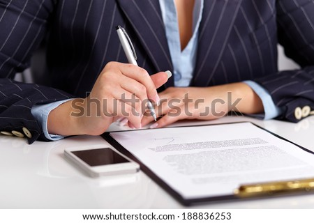 Young woman reads a signed contract on a white table - stock photo