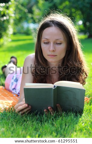 Young woman reads the book - stock photo