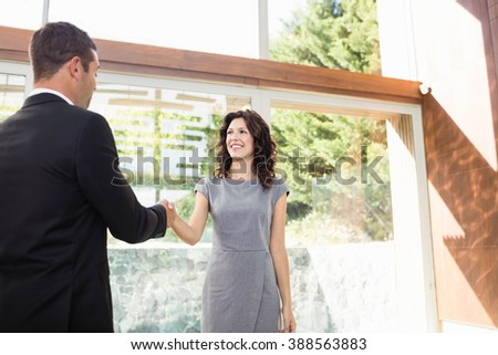 Young woman ready to buy new house shaking hands with estate-agent - stock photo