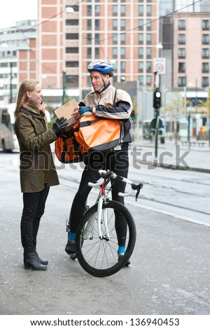 Young woman receiving a package from courier delivery man with bicycle and backpack - stock photo