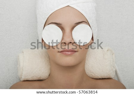 Young woman receiving face cleansing at beauty spa - stock photo