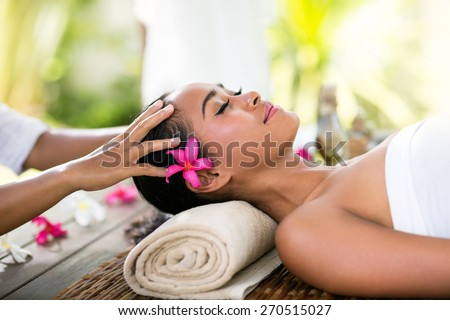 Young woman receiving recreation Balinese massage in spa - stock photo