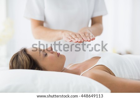 Young woman receiving reiki treatment at spa - stock photo