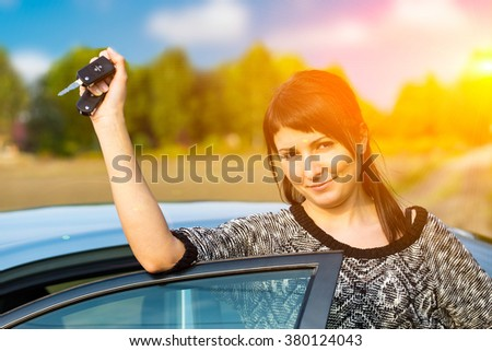 Young woman receiving the keys of her new car. Sunlight efect. - stock photo