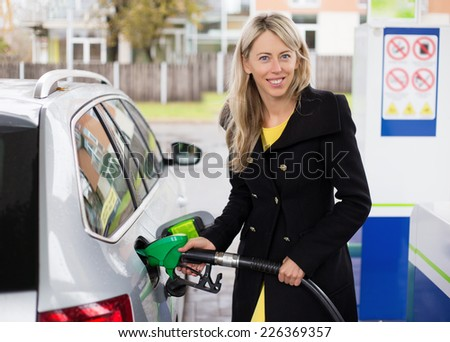 Young woman refilling car in gas station - stock photo