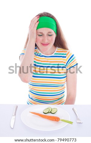 Young woman refuse to eat carrot and lettuce - stock photo
