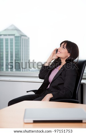 Young Woman Relaxed In Chair And Talking On Cell Phone In Office. - stock photo