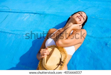 Young woman relaxing and enjoying at beach during tropical caribbean vacation travel. Beautiful girl in white bikini in Cancun, Mexico. - stock photo