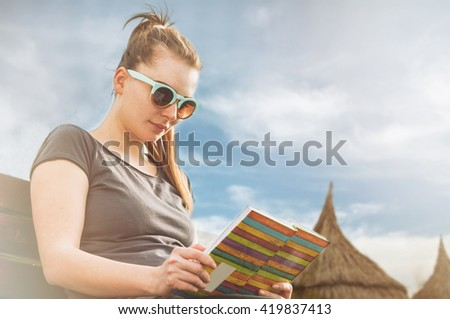 Young woman relaxing and reading a book on sunny day on the beach in her leisure time as  summer recreation concept - stock photo