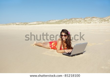 young woman relaxing and using laptop on wild beach - stock photo