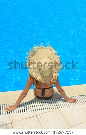 Young woman relaxing at the swimming pool in the summertime - stock photo