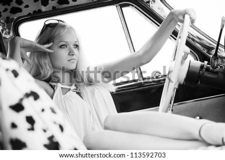 Young woman relaxing in a retro car - stock photo