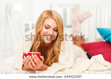 Young woman relaxing in bed with a cup of coffee - stock photo