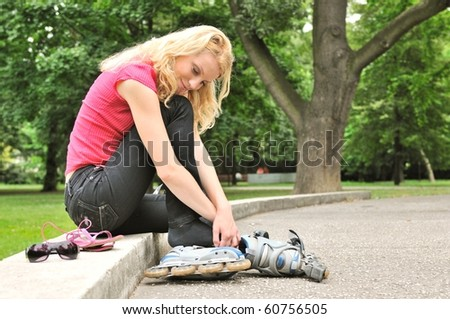 Young woman relaxing in park during rollerskating - trees in background - stock photo