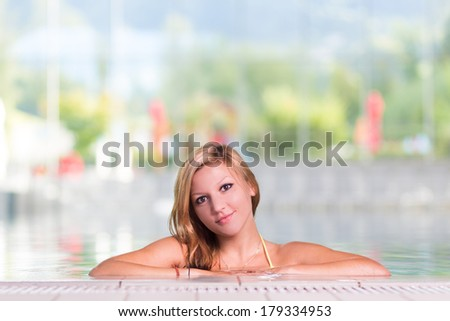 Young woman relaxing in the indoor swimming pool. - stock photo