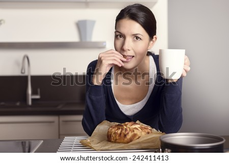 Young woman relaxing in the kitchen with a mug of coffee tasting her freshly baked apple cake  - stock photo