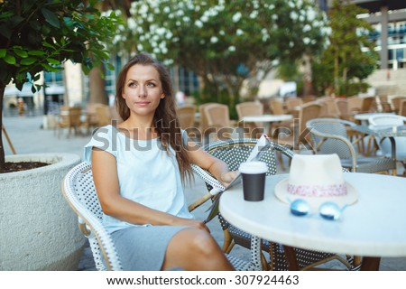 Young woman relaxing in the outdoor cafe - drinking coffee and reading the newspaper - stock photo