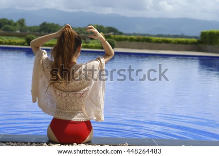 Young  woman relaxing in the pool. View from the back - stock photo