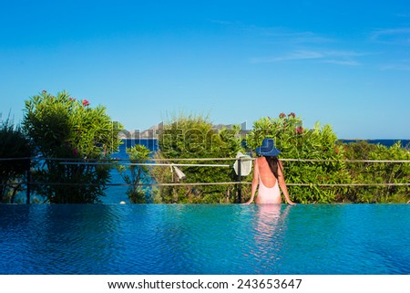 Young woman relaxing near the swimming pool - stock photo