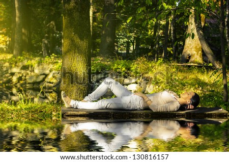 Young woman relaxing near water in summer season - stock photo