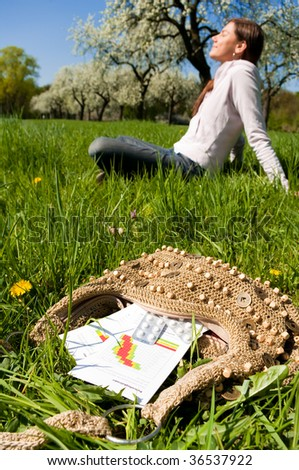 Young woman relaxing on a meadow with medicine in foreground. - stock photo
