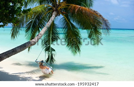 Young woman relaxing on a swing hanging on a palm at tropical white sand beach at Maldives - stock photo