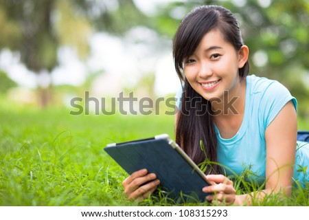 Young woman relaxing on grass with tablet and smiling at camera - stock photo