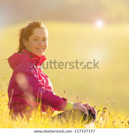 Young woman relaxing on green meadow - stock photo