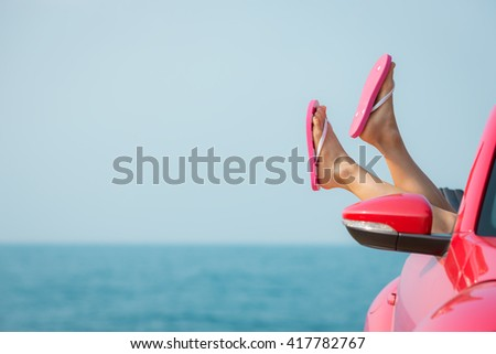 Young woman relaxing on the beach. Girl having fun in red cabriolet against blue sky background. Summer vacation and travel concept - stock photo