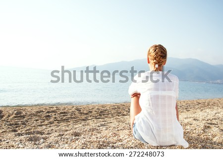 Young woman relaxing on the beach in the morning.  - stock photo