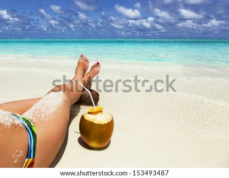 young woman relaxing on the beach with his legs crossed on a coco - stock photo
