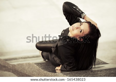 Young woman relaxing on the city sidewalk - stock photo