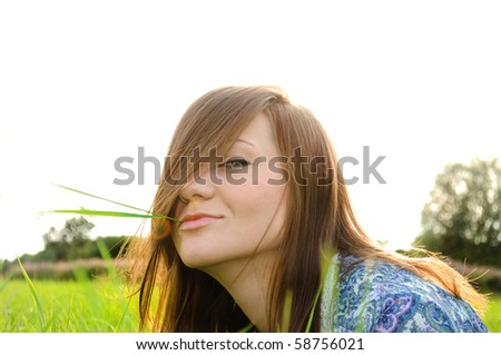 Young woman relaxing on the grass in the park - stock photo