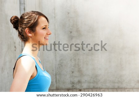 young woman resting after run by the wall in city with big smile. in blue shirt and clorfull shorts. - stock photo