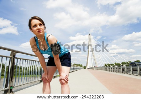 young woman resting after run. in blue sportswear. over the bridge - stock photo
