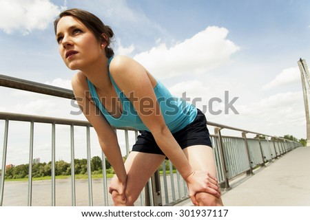 young woman resting after run. in blue sportswear. over the bridge. - stock photo