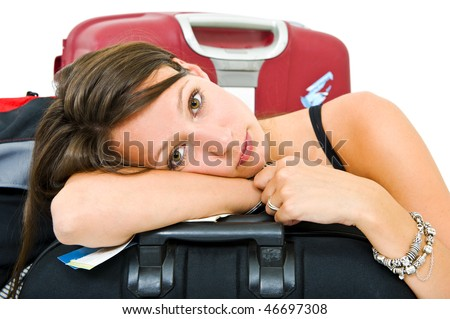 Young woman, resting her head on a suitcase, weary from traveling - stock photo