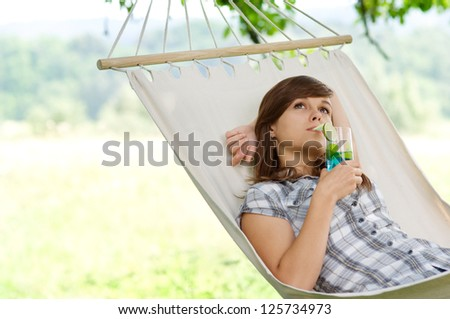Young woman resting in hammock - stock photo