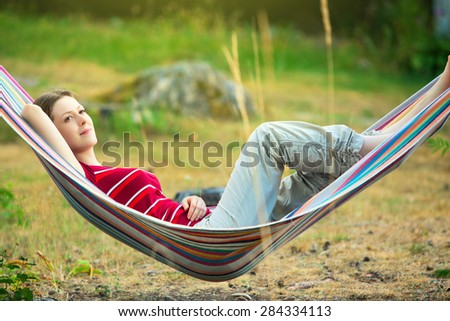Young woman resting in hammock. - stock photo