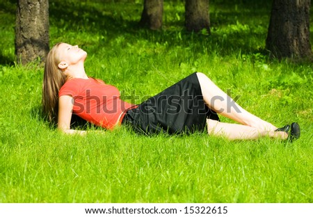 Young woman resting on green grass. - stock photo