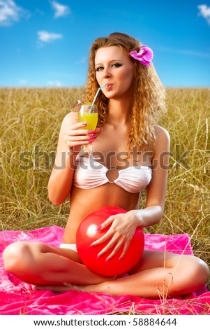 Young woman resting outdoors with cocktail. - stock photo