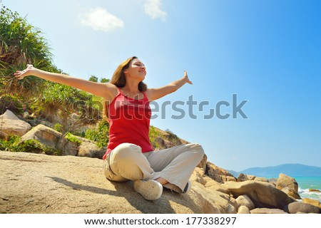 Young woman resting sitting on edge of a cliff - stock photo