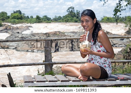 Young woman resting with coconut at the waterfall - stock photo