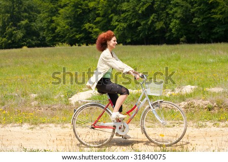 Young woman riding a bike on a country road - stock photo